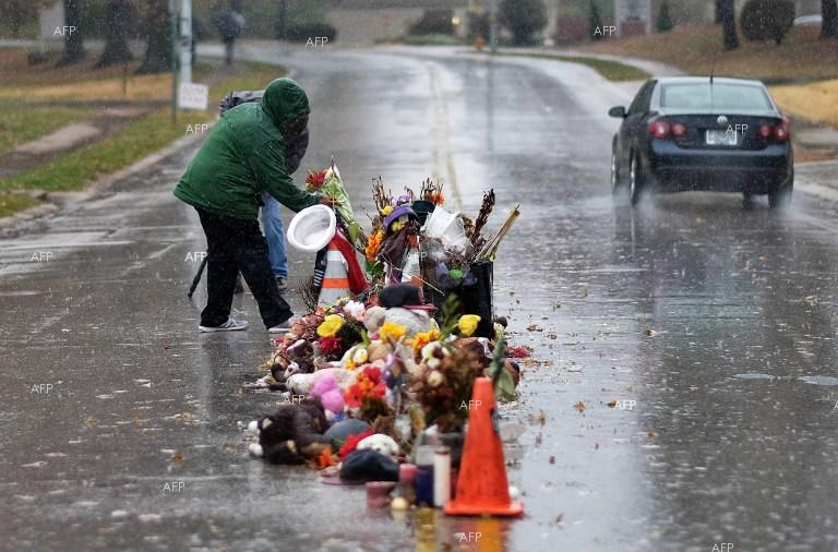 People leave flowers at the place where 12-year-old boy was fatally shot by police in Cleveland, Ohio, after waving a toy gun on a playground