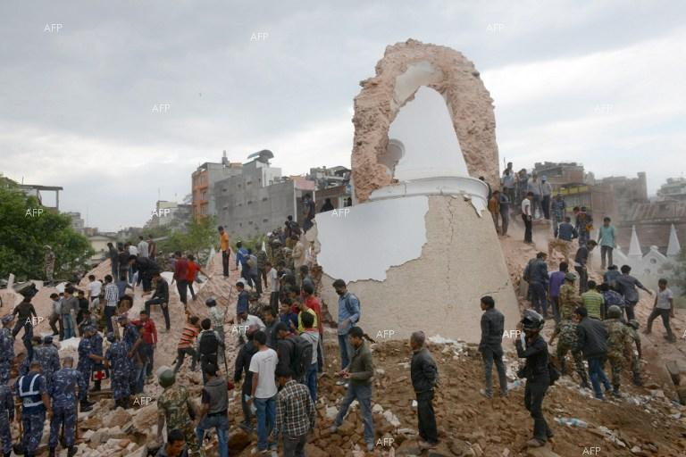 Nepalese rescue members and onlookers gather at the collapsed Dharahara Tower in Kathmandu on April 25, 2015.