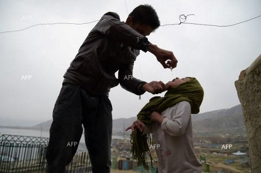 An Afghan health worker administers the polio vaccine to a child on the second day of a vaccination campaign in Kabul on February 28, 2017