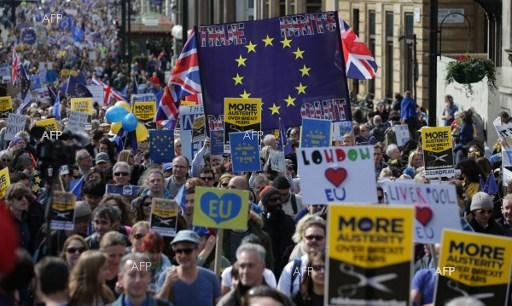 Demonstrators hold placards and wave EU flags as they participate in an anti Brexit, pro-European Union (EU) march in London on March 25, 2017.
