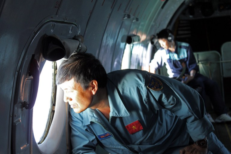 Vietnamese military officers search for missing Malaysian plane.