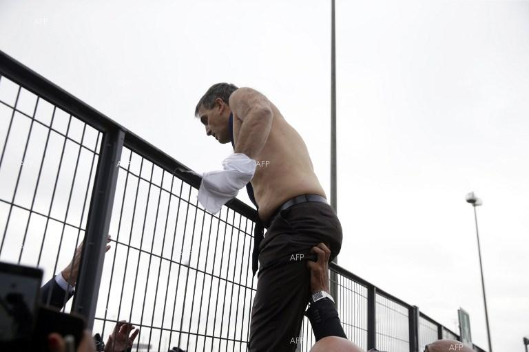 Director of Air France in Orly Pierre Plissonnier and Air France Human Resources Director Xavier Broseta, shirtless, walk away from demonstrators, accompanied by anti-riot police officers, after several hundred of employees invaded the offices of Air Fran