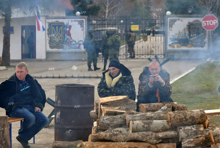 Pro-Russian activists help Russian forces for the seizure of the Ukrainian military base in Perevalne, Crimea.