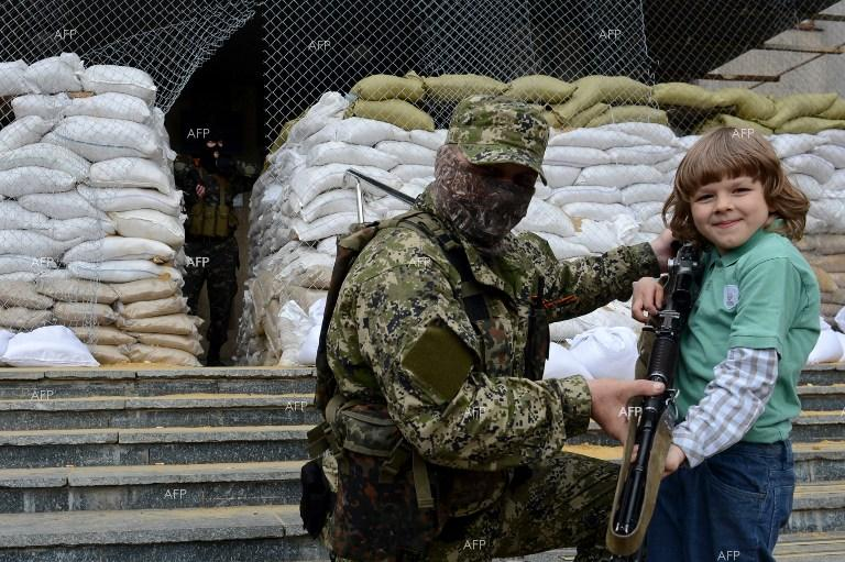 Eastern Ukraine. Boy holding the wepon of a person guarding a public building in Slavyansk poses for a photo.