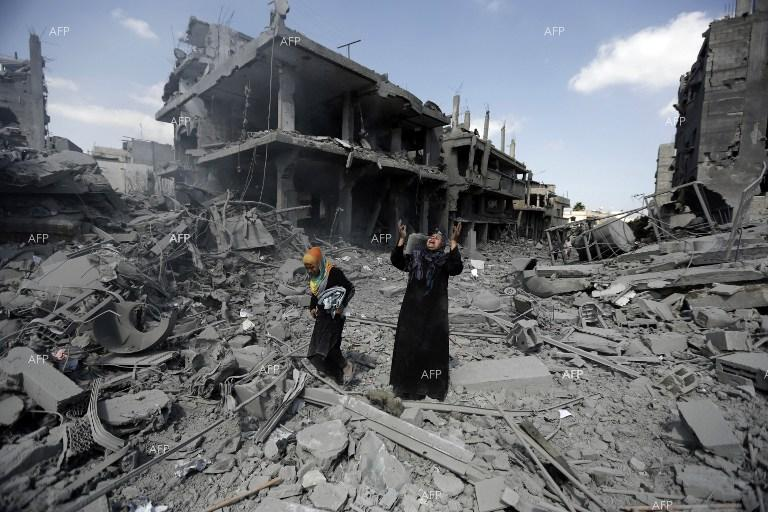 Palestinian woman in front of ruined homes in the Gaza Strip.
