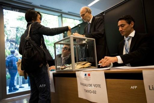 A French citizen casts her ballot in the first round of French presidential election at a polling station at the French embassy in Tokyo on April 23, 2017.