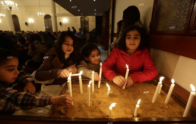 Christians from Iraq, Syria and Lebanon light candles in a church in a Beirut suburb.